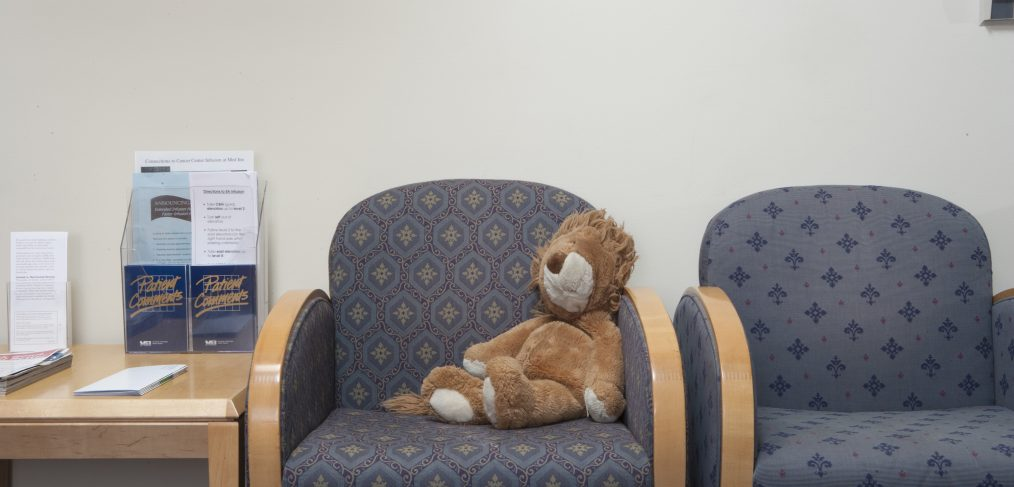 In waiting room, with hospital seats - and a teddy bear sitting on one of them.